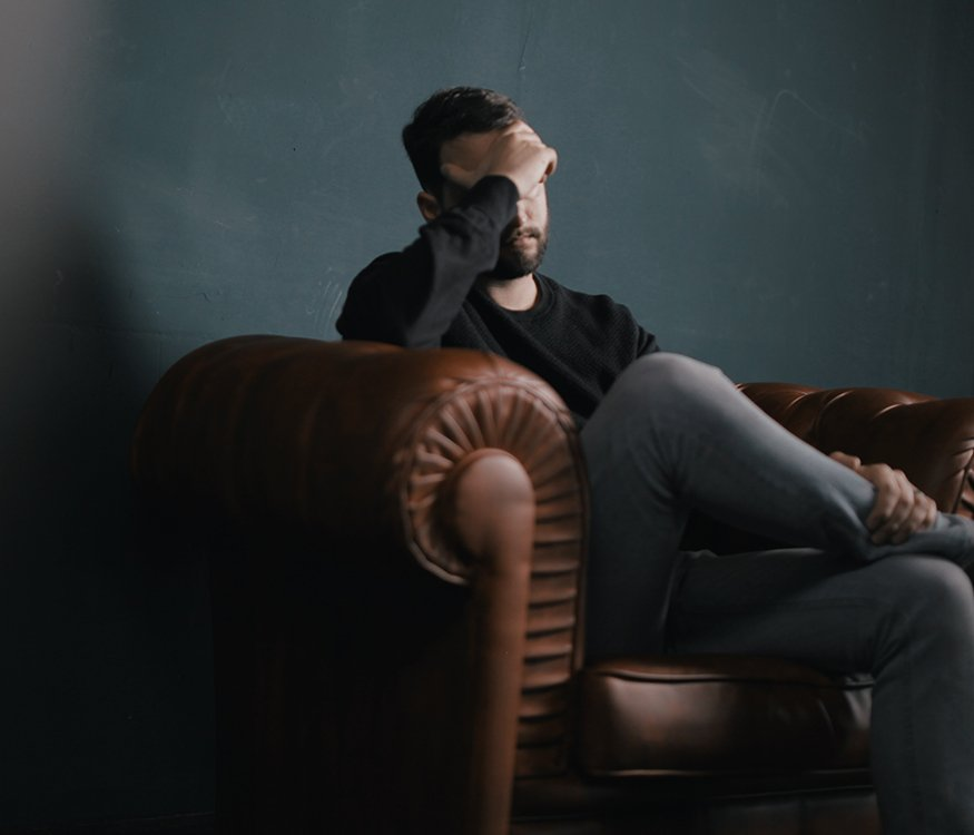 Man experiencing grief sitting on a couch