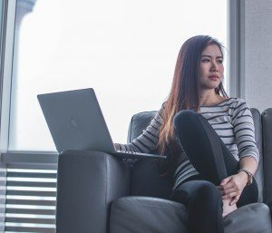 Woman sitting on the couch worried about work